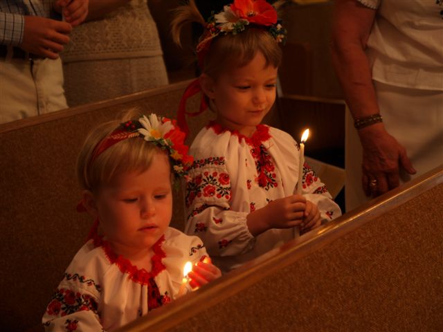 Girls in traditional Ukrainian dress hold candles