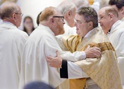 Fr. Dennis Smith embraces a newly ordained priest